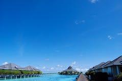 Molhe bungalows e o oceano azul do céu e o azul Imagem de Stock