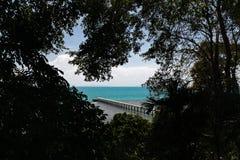 Molhe concreto cercado pela floresta tropical com oceano azul Imagens de Stock