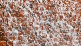 Molhe a conexão em cascata de fluxo sobre tijolos ásperos no laço video estoque