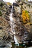 Molhe a conexão em cascata sobre rochas, cachoeira e cores do outono nas árvores das montanhas, as amarelas e as vermelhas Fotografia de Stock Royalty Free