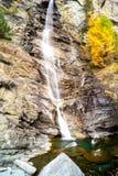 Molhe a conexão em cascata sobre rochas, cachoeira e cores do outono nas árvores das montanhas, as amarelas e as vermelhas Imagem de Stock