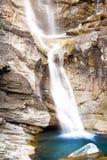 Molhe a conexão em cascata sobre rochas, cachoeira e cores do outono nas árvores das montanhas, as amarelas e as vermelhas Foto de Stock