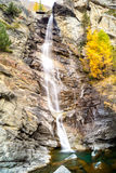 Molhe a conexão em cascata sobre rochas, cachoeira e cores do outono nas árvores das montanhas, as amarelas e as vermelhas Fotos de Stock Royalty Free