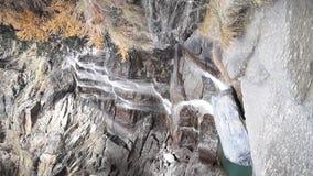 Molhe a conexão em cascata sobre rochas, cachoeira e cores do outono nas árvores das montanhas, as amarelas e as vermelhas video estoque