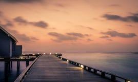 Molhe de madeira e nascer do sol surpreendente em Maldivas Imagem de Stock Royalty Free