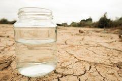 Molhe em um frasco na terra vazia seca e da quebra do fundo imagem de stock royalty free