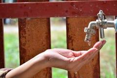 Molhe a gota da torneira de água à mão da pessoa, da água menos e do crit Imagem de Stock