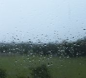 Molhe gotas da chuva em um vidro de janela foto de stock