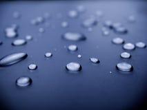 Molhe gotas no fundo azul Fotografia de Stock Royalty Free