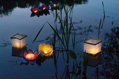 Molhe lanternas amarelas ardentes no lago entre a grama alta Fotografia de Stock
