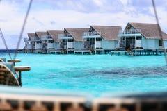 Molhe o bungalow construído no mar azul em Maldivas Imagem de Stock