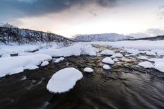 Molhe o córrego com rochas em uma paisagem do inverno no crepúsculo Imagens de Stock