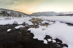Molhe o córrego com rochas em uma paisagem do inverno no crepúsculo Foto de Stock