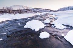 Molhe o córrego com rochas em uma paisagem do inverno no crepúsculo Fotos de Stock Royalty Free