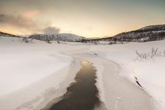 Molhe o córrego com rochas em uma paisagem do inverno no crepúsculo Fotografia de Stock Royalty Free