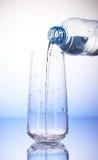 Molhe o derramamento da garrafa plástica no vidro bebendo vazio fotos de stock royalty free