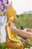 Molhe o derramamento e a estátua dourada da Buda no festival de Songkran trad Imagem de Stock Royalty Free