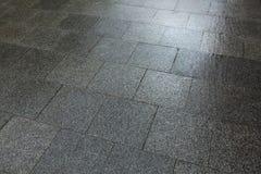 Molhe os pavimentos feitos de microplaquetas de um mármore após a chuva Fotos de Stock
