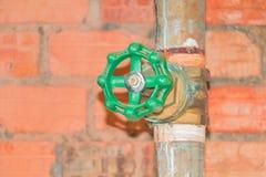Molhe a tubulação velha de aço da torneira da junção do encanamento da válvula com o botão verde no fundo do tijolo imagens de stock