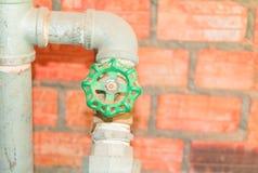 Molhe a tubulação velha de aço da torneira da junção do encanamento da válvula com o botão verde no fundo do tijolo foto de stock royalty free