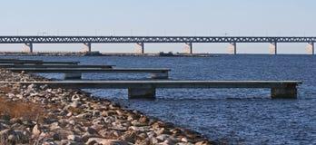 Molhes pequenos e uma ponte longa Fotografia de Stock