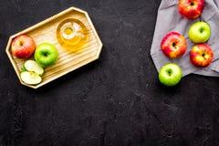 Molho claro da salada Vinagre de sidra de maçã na garrafa entre maçãs frescas no espaço preto da cópia da opinião superior do fun Fotografia de Stock Royalty Free