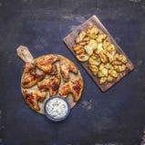 Molho de alho grelhado delicioso das asas de galinha e batatas fritadas com aneto no fim rústico de madeira da opinião superior d Foto de Stock