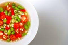 Molho de peixes e pimentões verdes e vermelhos tailandeses no copo branco Imagem de Stock