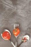 Molho de tomate, cereja, especiarias na forquilha e colheres em uma obscuridade Imagens de Stock