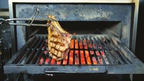 Molho do BBQ na carne em um bife do ar livre da grade Tiro ascendente próximo do bife grelhado chama do osso do BBQ T As chamas a video estoque
