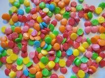 Molho dos confeitos com os círculos coloridos dispersados na tabela fotografia de stock royalty free
