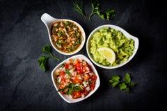 Molhos latino-americanos tradicionais Guacamole, salsa, pimentão Pebre, fundo da ardósia Imagem de Stock Royalty Free