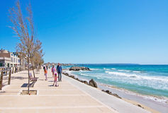 Molinar seaside sidewalk with family. PORTIXOL/MOLINAR, MALLORCA, BALEARIC ISLANDS, SPAIN - APRIL 10, 2016: Family with kids on scooters with helmets on the Stock Photos