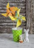 Molinillo de viento de papel hecho en casa, conejitos de cerámica en una tabla de madera rústica ligera Todavía de Pascua vida Imagen de archivo libre de regalías