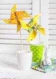 Molinillo de viento de papel hecho en casa, conejo de cerámica, libreta del vintage y tazas de papel Todavía de Pascua vida Imágenes de archivo libres de regalías