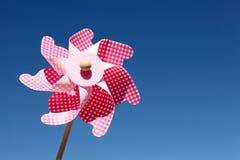 Molinillo de viento del juguete contra el cielo azul Imagen de archivo