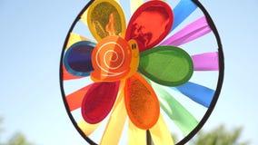 Molinillo de viento del juguete multicolor, girado por el viento contra un cielo azul decoraciones coloreadas para un partido de  almacen de metraje de vídeo