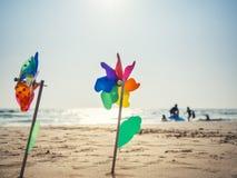 Molinillo de viento en la playa de la arena con la familia el vacaciones de verano del fondo Imagen de archivo