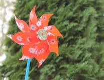 Molinillo de viento rojo en un jardín Imágenes de archivo libres de regalías
