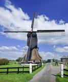 Molino bajo del wip de la vela en un pólder con un cielo azul y nubes formadas dramáticas, Países Bajos Foto de archivo