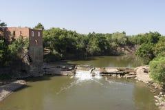 Molino de agua abandonado en un río con la pequeña cascada Fotografía de archivo libre de regalías