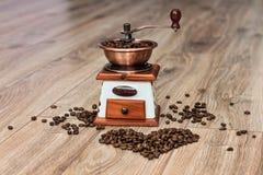 Molino de café en el piso de madera con el hogar Fotos de archivo