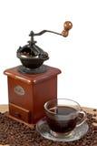 Molino de café manual retro en los granos de café asados con una taza de café Fotos de archivo
