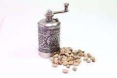 Molino de café oriental árabe con los granos del café verde en el fondo blanco Fotos de archivo libres de regalías
