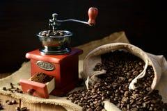 Molino de café y granos de café en fondo oscuro Fotografía de archivo