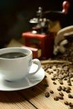 Molino de café y granos de café en fondo oscuro Imágenes de archivo libres de regalías