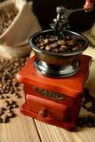 Molino de café y granos de café en fondo oscuro Fotos de archivo