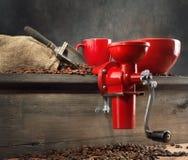 Molino de café y granos de café rojos Fotografía de archivo libre de regalías