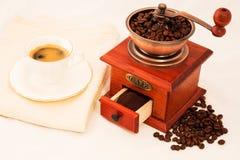 Molino de café y taza de café retros en el fondo blanco Fotos de archivo