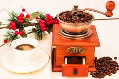 Molino de café y taza de café retros en el fondo blanco Imagenes de archivo